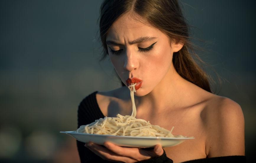 Čo je intuitívne stravovanie? Žena vcucáva špagety ztaniera