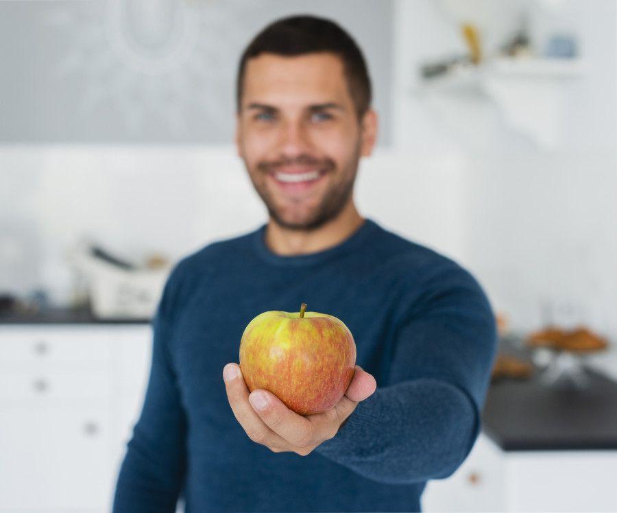 Chlap ponúka jablko