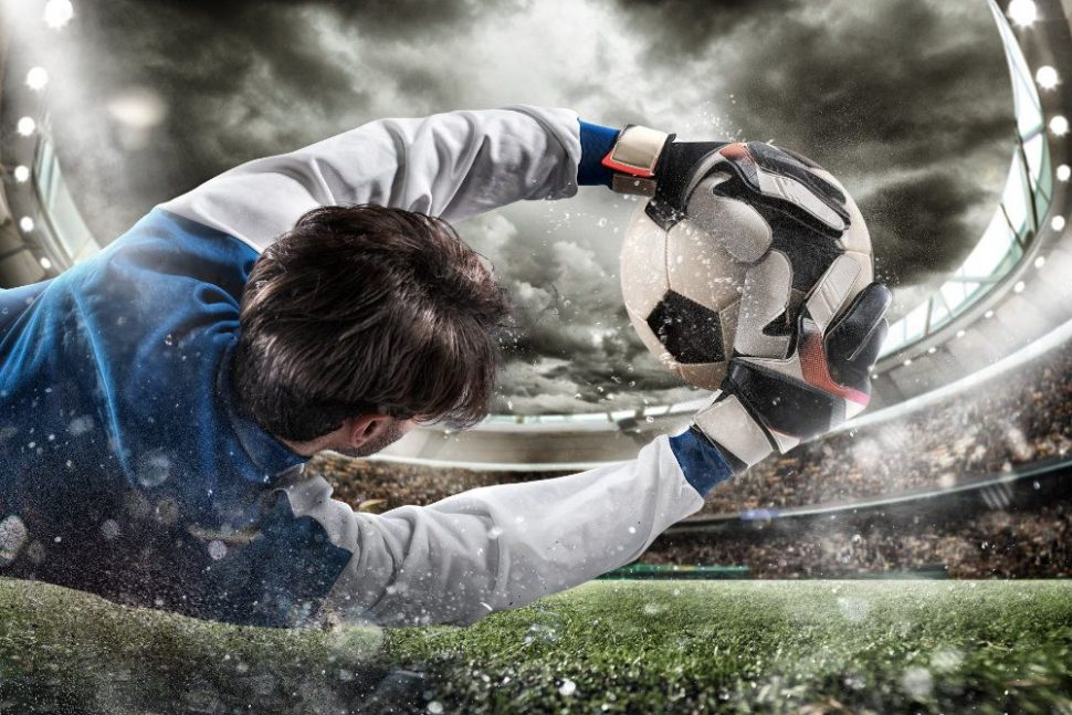 Brankár má futbalové rukavice a chytá loptu na zemi
