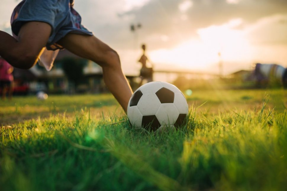 Futbalova lopta a chlapec, podvečer