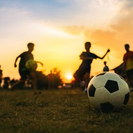 Deti hrajú futbal pri západe slnka