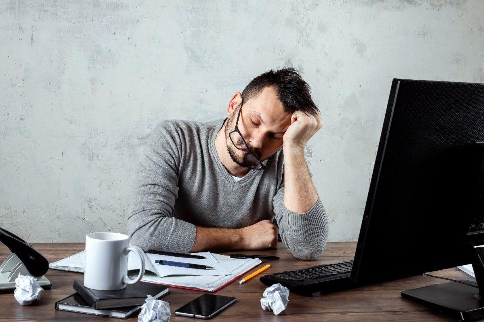 Unavený muž spí za pracovným stolom