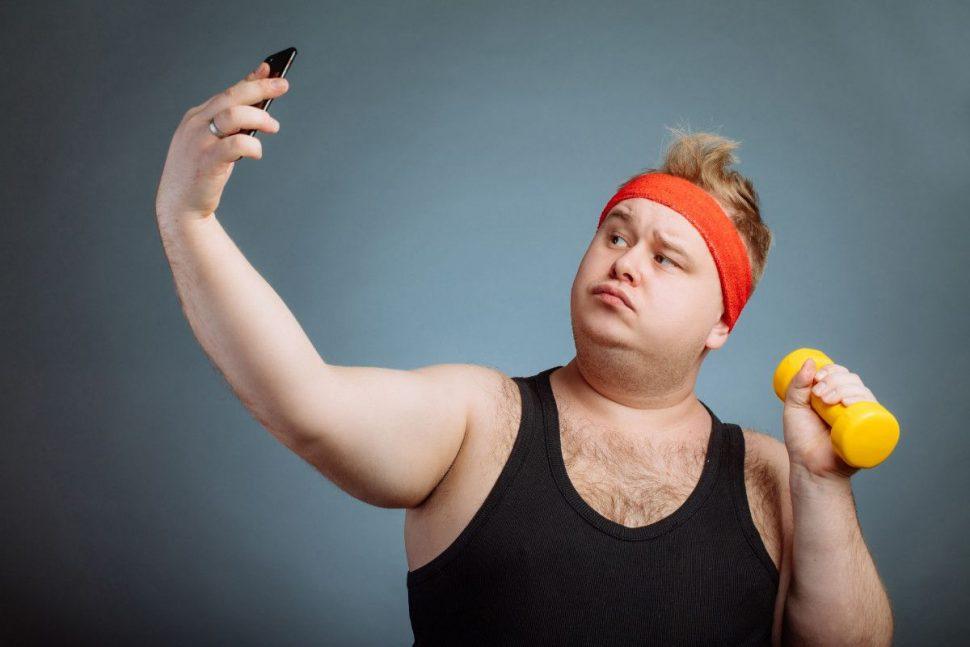 Tučný muž robí selfie s činkou