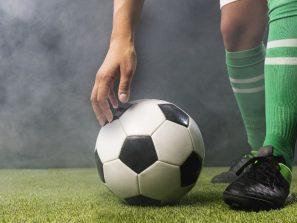 Futbalové ihrisko, futbalista a lopta, detail