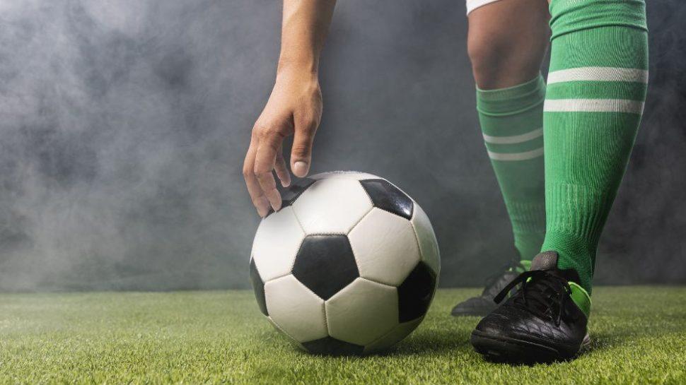 Futbalové ihrisko, futbalista alopta, detail